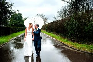 Rainy Wedding couple photo with umbrella in country lane