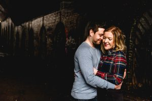 Couple laughing under the canal bridge on engagement shoot.