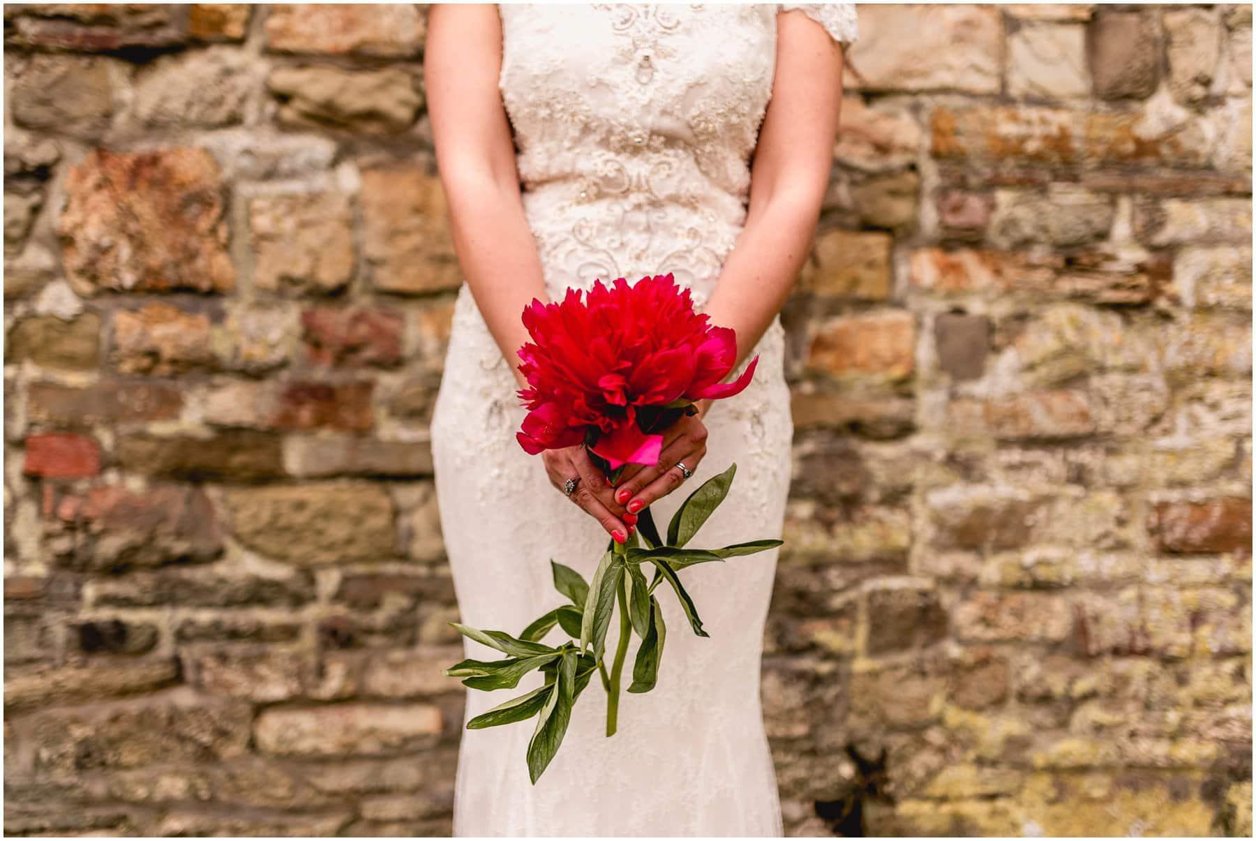 Bridal bouquet single stem large red flower.